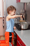 Child cooking porridge Royalty Free Stock Image
