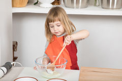 Child cooking stirring yogurt. Three years old child with orange and red apron making and cooking a sponge cake at kitchen home, stirring yogurt with wooden Stock Photos