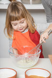 Child cooking whipping yogurt. Three years old child with orange and red apron making and cooking a sponge cake at kitchen home, whipping yogurt with metal Stock Photography