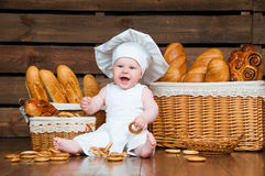 Child cooks a croissant in the background of baskets with rolls and bread. Stock Image