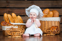 Child cooks a croissant in the background of baskets with rolls and bread. Stock Photography