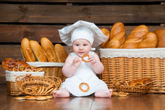 Child cooks a croissant in the background of baskets with rolls and bread. Stock Images