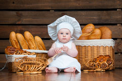 Child cooks a croissant in the background of baskets with rolls and bread. Stock Photo