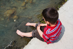 Child cooling feet in water Royalty Free Stock Photos
