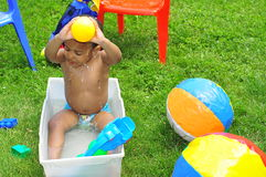Child cooling off with water. Very happy boy pouring water on head to keep cool in hot  summer sun Stock Photo