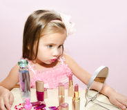 Child cosmetics  Cute little girl looking in the mirror Stock Images