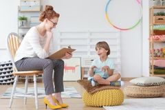 Child counselor during psychotherapy session. Cheerful young kid talking with helpful child counselor during psychotherapy session in mental health center for Stock Photo