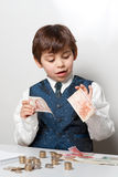 Child counting money. And taking notes Stock Image
