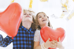 Child couple with balloon hearts Royalty Free Stock Photography
