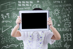 Child cover her face with tablet in class. Female elementary school student standing near the blackboard and cover her face with tablet Royalty Free Stock Images