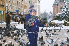 Child covered with doves while other people pass in the background