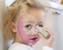 Child covered in lipstick. A child painting her face with lipstick royalty free stock photography
