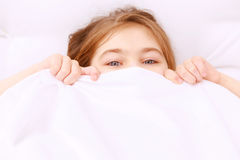 Child covered with white blanket. Smile with eyes. Little child covered with white blanket up to its eyes royalty free stock photo