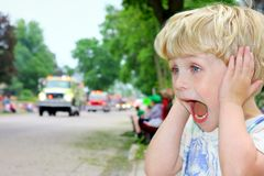 Child Covering Ears at Loud Parade. A young blonde boy covers his ears and looks excited as ambulances and fire trucks drive by in a parade Stock Images