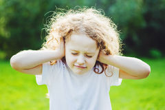 Child covering her ears. Royalty Free Stock Photo
