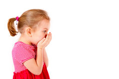 Child covers her mouth with  hands Stock Photo
