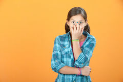 Child Covers Her Own Face. Giggling Latina child on orange background covers her face Royalty Free Stock Image