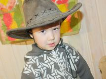 The child in a cowboy hat is smiling broadly. A little boy in a. Cowboy hat is having fun. Smile to the ears Stock Photography