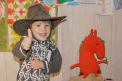 The child in a cowboy hat is smiling broadly. A little boy in a. Cowboy hat is having fun. Smile to the ears. the boy is showing a gesture-super Royalty Free Stock Images