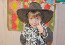 The child in a cowboy hat is smiling broadly. A little boy in a. Cowboy hat is having fun. Smile to the ears. the boy is showing a gesture-super Royalty Free Stock Photos