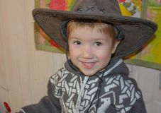 The child in a cowboy hat is smiling broadly. A little boy in a. Cowboy hat is having fun. Smile to the ears Stock Photos
