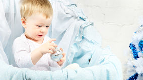 Child in Cradle. Baby in cradle playing with christmas ball stock photo