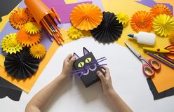 The child creates a gift box of a black cat. A party for Halloween. Children`s hands make a master class. Craft for kids. Materials for creativity of orange royalty free stock photography