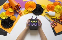 The child creates a gift box of a black cat. A party for Halloween. Children`s hands make a master class. Craft for kids. Materials for creativity of orange royalty free stock photos