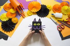 The child creates a gift box of a black cat. A party for Halloween. Children`s hands make a master class. Craft for kids. Materials for creativity of orange royalty free stock images