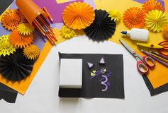 The child creates a gift box of a black cat. A party for Halloween. Children`s hands make a master class. Craft for kids. Materials for creativity of orange royalty free stock image