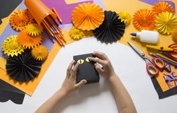 The child creates a gift box of a black cat. A party for Halloween. Children`s hands make a master class. Craft for kids. Materials for creativity of orange stock photos