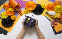 The child creates a gift box of a black cat. A party for Halloween. Children`s hands make a master class. Craft for kids. Materials for creativity of orange stock image
