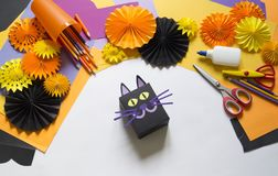 The child creates a gift box of a black cat. A party for Halloween. Children`s hands make a master class. Craft for kids. Materials for creativity of orange stock images