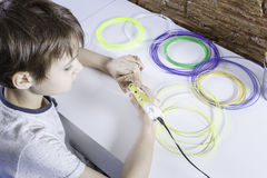 Child creating with 3D printing pen. Boy making new item. Creative, technology, leisure, education concept. Happy child creating with 3D printing pen. Kid making Stock Image