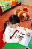 Child creativity. Little six year old girl alone at home, deeply concentrated on the painting she makes, with her big, protecting toy dog in the background Royalty Free Stock Image