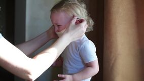Child cries and does not want to wear a protective mask during the epidemic