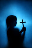 Child and cross. A shadow child hold the cross with blue background stock photos