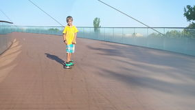 Child cruising, down a bridge on a pennyboard, flares, slow motion stock footage