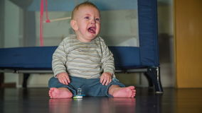 Child crying to get mother attention. On this slow motion high quality footage is little sad baby boy sitting on the wooden floor and crying for mothers stock video footage