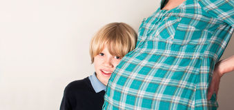 Child cuddling his pregnant mother Stock Photo