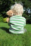 Child cuddling teddy bear Stock Image