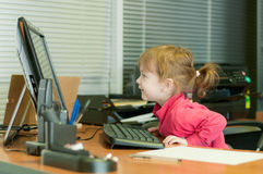The child with curiosity looks in the computer mon Stock Photography