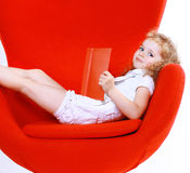Child curly cute girl resting in a chair reading book Royalty Free Stock Photos