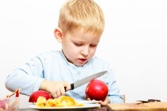 Child cut apple with a kitchen knife, cooking. Royalty Free Stock Image