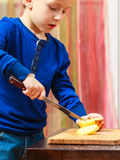 Child cut apple with a kitchen knife, cooking. Stock Photos