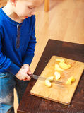 Child cut apple with a kitchen knife, cooking. Stock Images