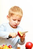 Child cut apple with a kitchen knife, cooking. Stock Photography