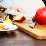 Child cut apple with a kitchen knife Stock Image