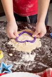 Child cut out cookies for baking Royalty Free Stock Image