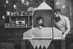 Child cute boy play cosmonaut, astronaut. Kid happy sit in cardboard hand made rocket. Boy play with dad, father, little. Cosmonaut sit in rocket made out of stock image